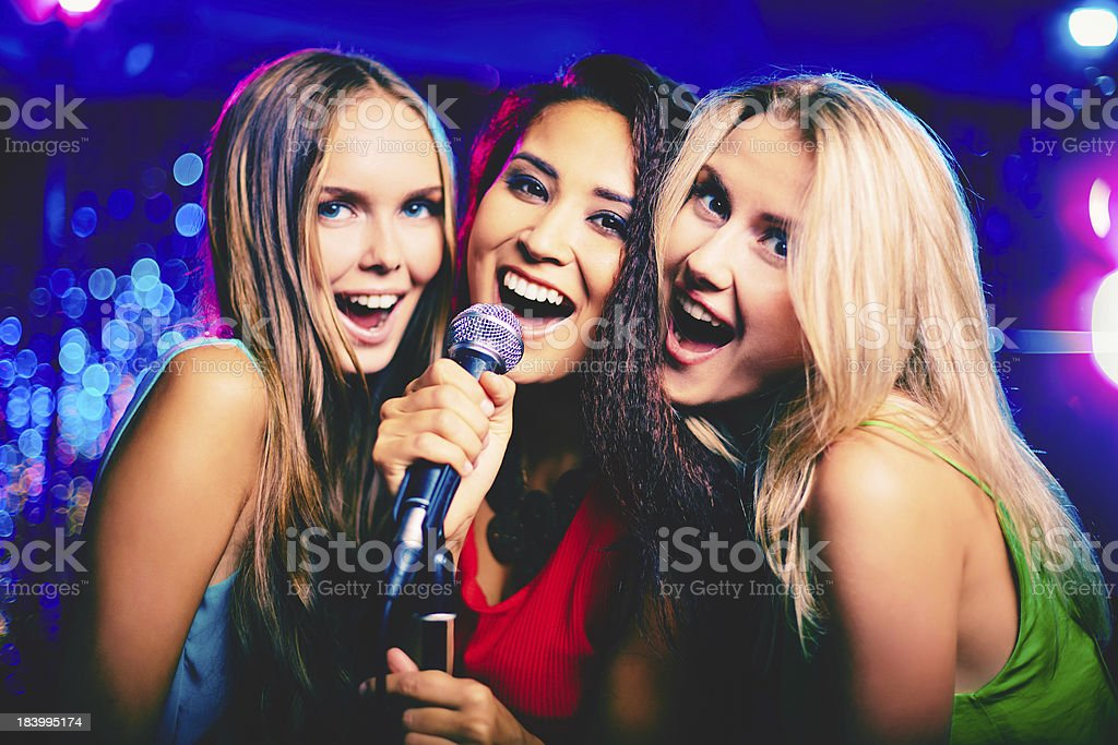 Three young girls performing karaoke stock photo