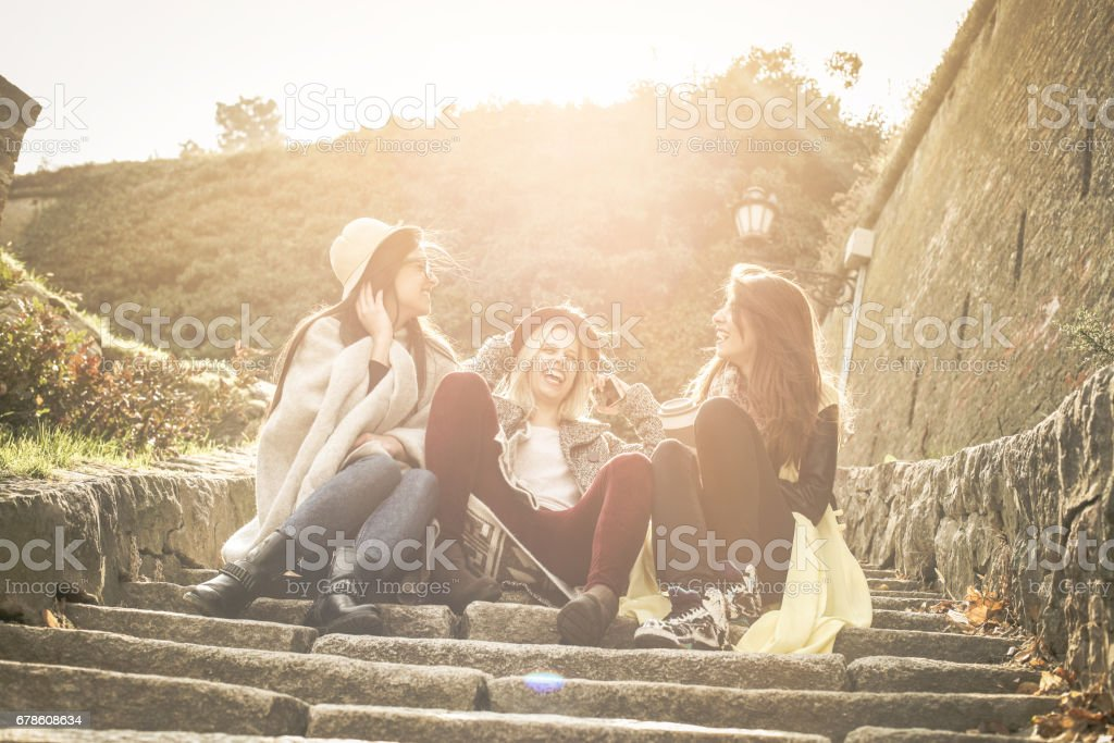 Three young girls sitting on the stairs at the public park. stock photo
