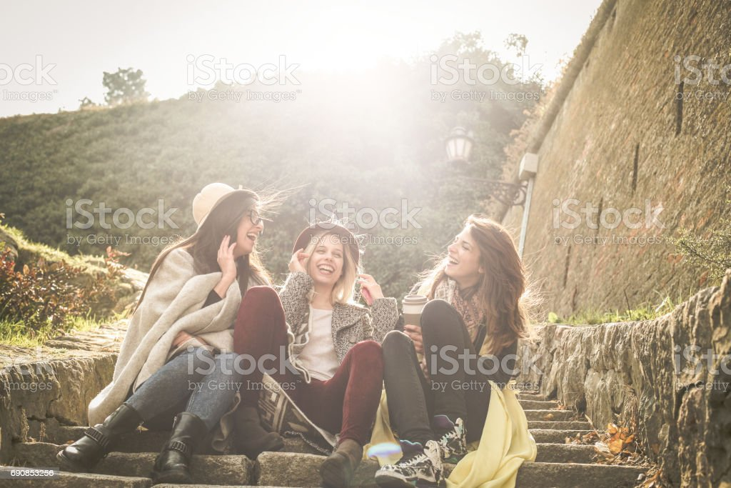 Three young girls sitting on the stairs at the public park. Three young girls sitting on the stairs at the public park an having conversation. stock photo