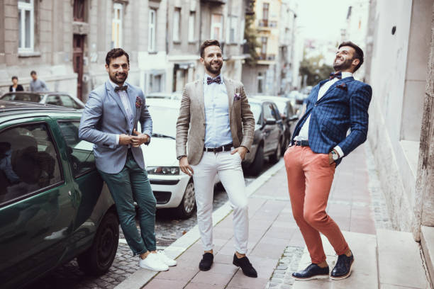 Three young good looking tailors laughing on the street stock photo