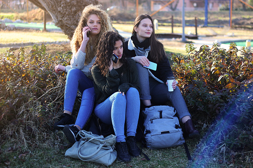 700702502 istock photo Three young happy girls in public park 1211171903