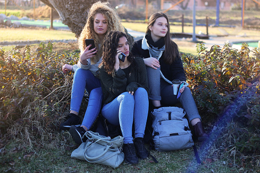 700702502 istock photo Three young happy girls in public park 1211172081