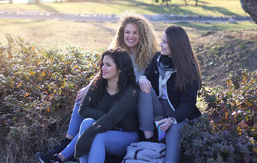 700702502 istock photo Three young happy girls in public park 1211172837