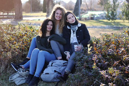 700702502 istock photo Three young happy girls in public park 1211173230