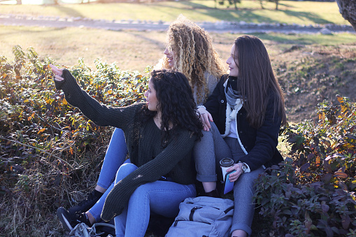 700702502 istock photo Three young happy girls in public park 1211173248