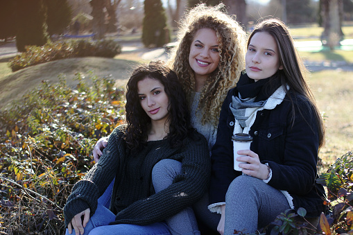 700702502 istock photo Three young happy girls in public park 1211173983