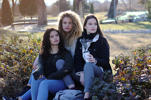 700702502 istock photo Three young happy girls in public park 1211174532