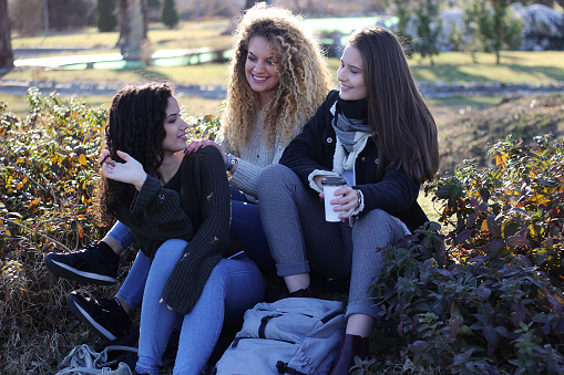 700702502 istock photo Three young happy girls in public park 1211174919