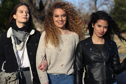 700702502 istock photo Three young happy girls in public park 1211176881