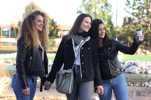 700702502 istock photo Three young happy girls in public park 1211176927