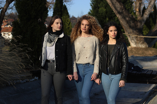 700702502 istock photo Three young happy girls in public park 1211176990