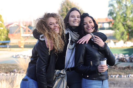 700702502 istock photo Three young happy girls in public park 1211176994