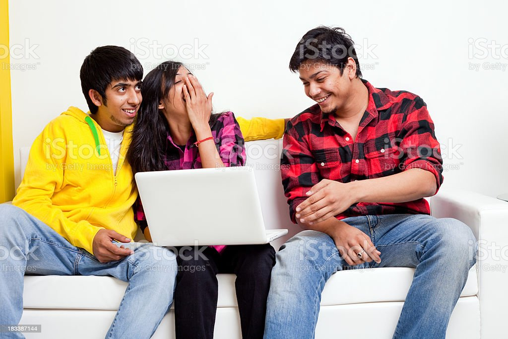 Three Young Indian Cheerful Friends with Laptop on Sofa Couch stock photo