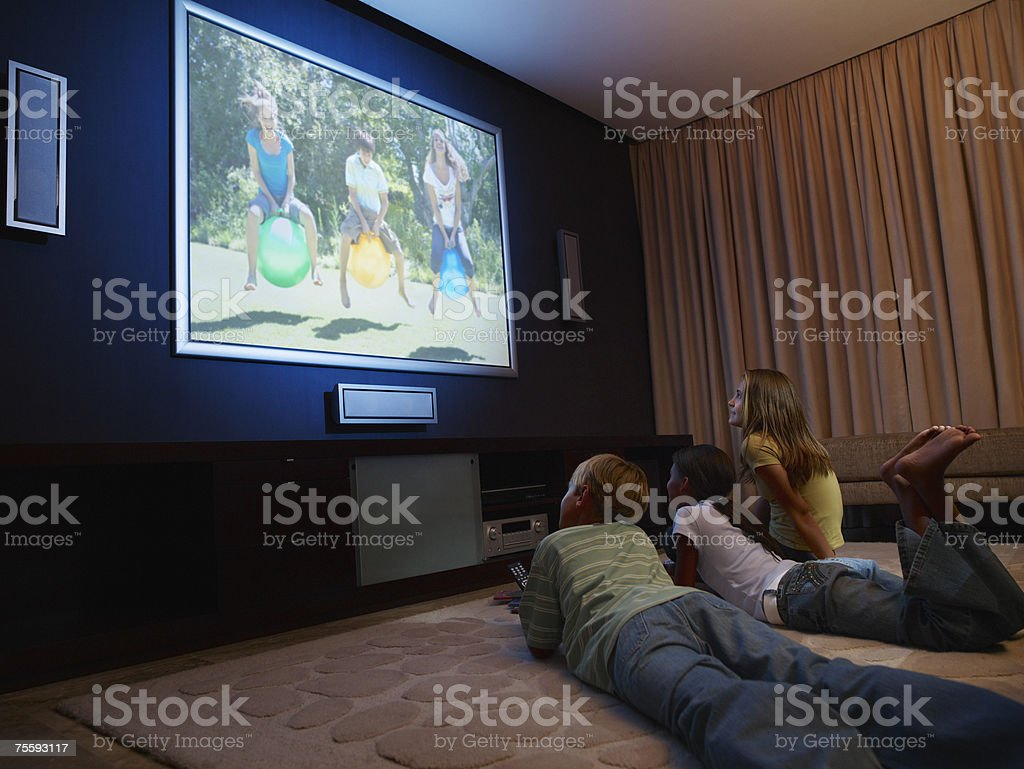 Three young kids watching a large wall television stock photo