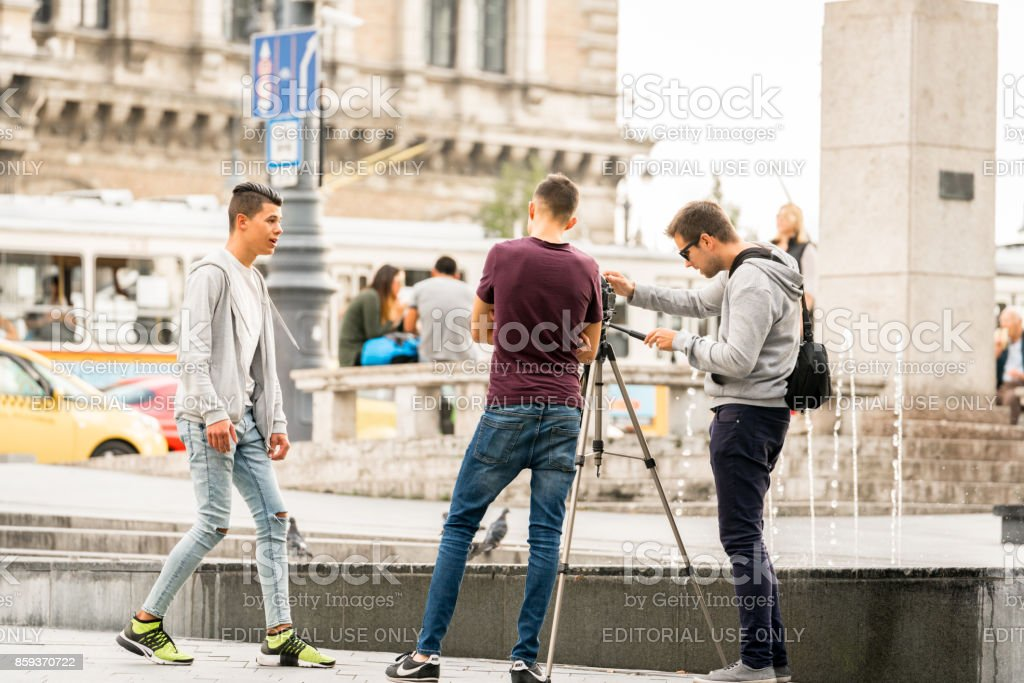 Three young men filming each other at a city square in Budapest. royalty-free stock photo