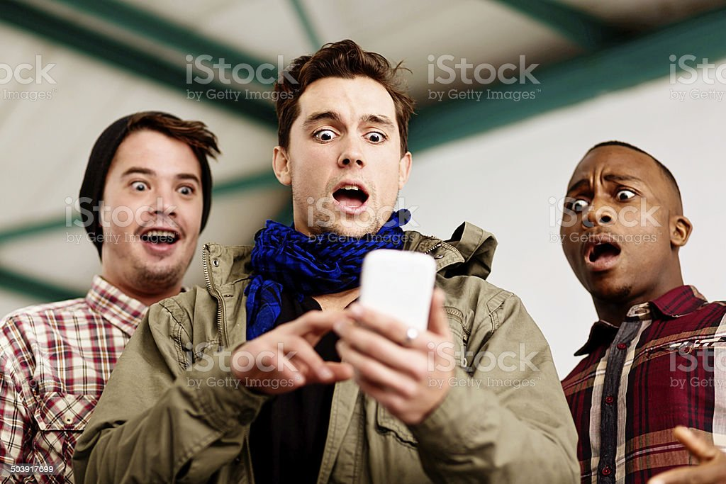 Three young men gaze, horrified, at image on cellphone stock photo