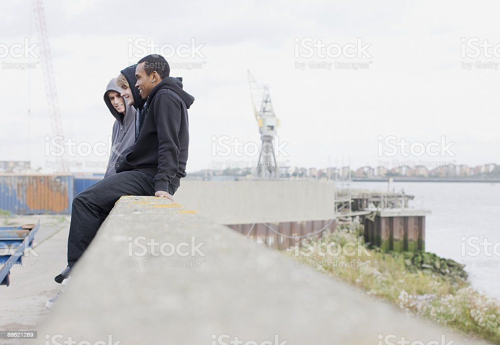 Three young men in hoodies sitting on wall stock photo