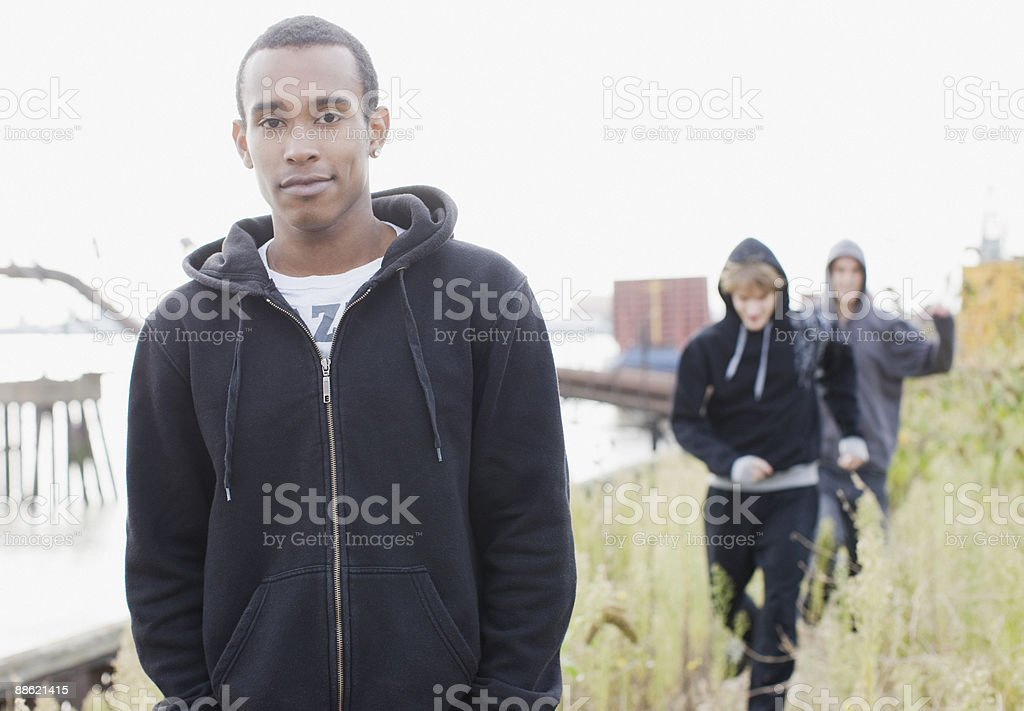 Three young men walking through urban field stock photo