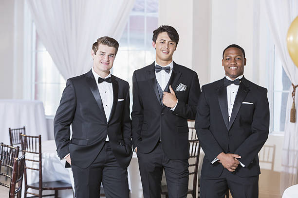 Three young men wearing tuxedos A group of three multi-ethnic young men wearing tuxedos, standing in a row, smiling at the camera. They are at a party, prom, a wedding or some other special formal event. tuxedo stock pictures, royalty-free photos & images