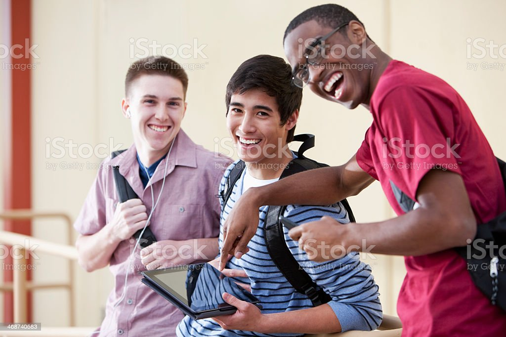Three young men with digital tablet stock photo