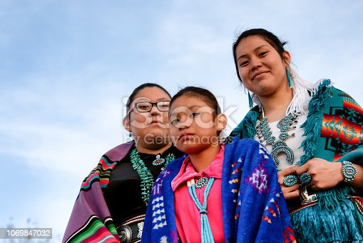 Three beautiful, proud and traditional Native Amerian Navajo sisters in traditional clothing posing outside in Monument Valley Arizona