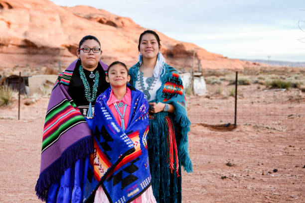 Three Young Navajo Sisters in Monument Valley Arizona Three beautiful, proud and traditional Native Amerian Navajo sisters in traditional clothing posing outside in Monument Valley Arizona indigenous peoples of the americas stock pictures, royalty-free photos & images