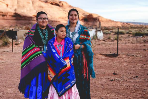 drei leben junge navajo schwestern in monument valley in arizona - kleidung amerikanischer ureinwohner stock-fotos und bilder