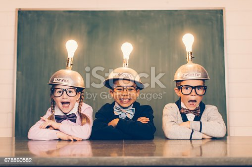Three young nerds sit in a classroom setting with a thinking cap on their heads. They are suprised and smiling as their light bulbs are lit as the new ideas are flowing. They're wearing cardigans and bow ties. Learning is fun when you have ideas.