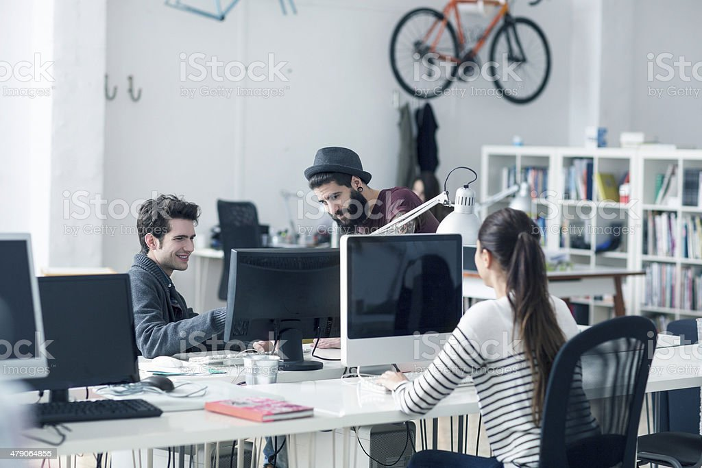 Three young people at desk royalty-free stock photo