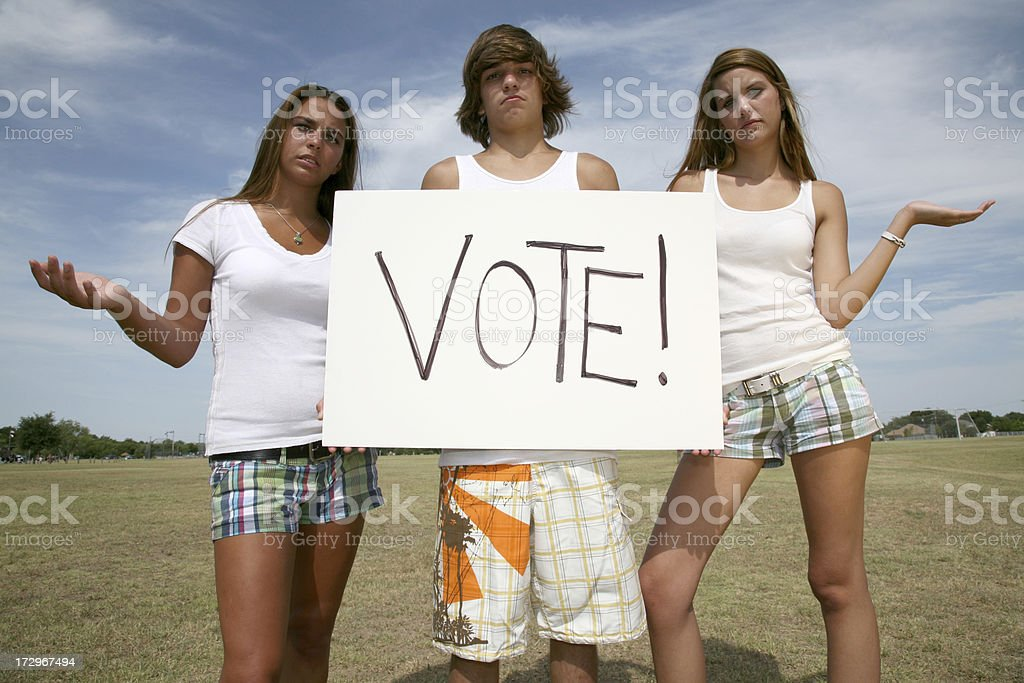 Three young people dressed casually holding a vote sign. royalty-free stock photo