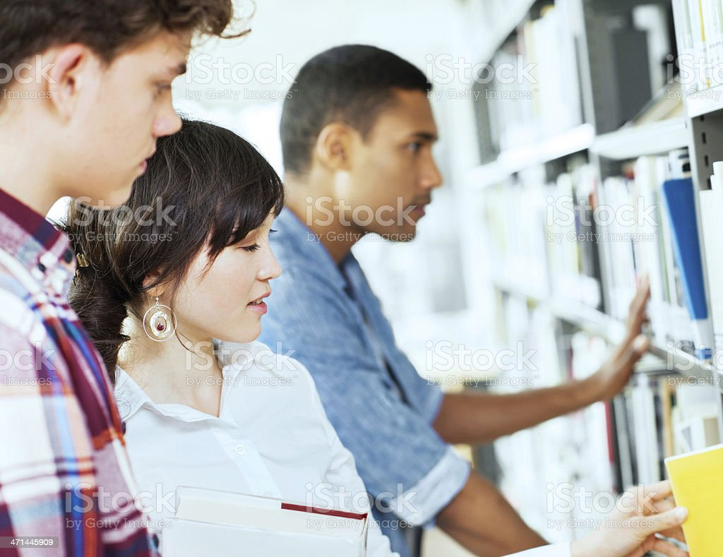 Three young people in library. royalty-free stock photo