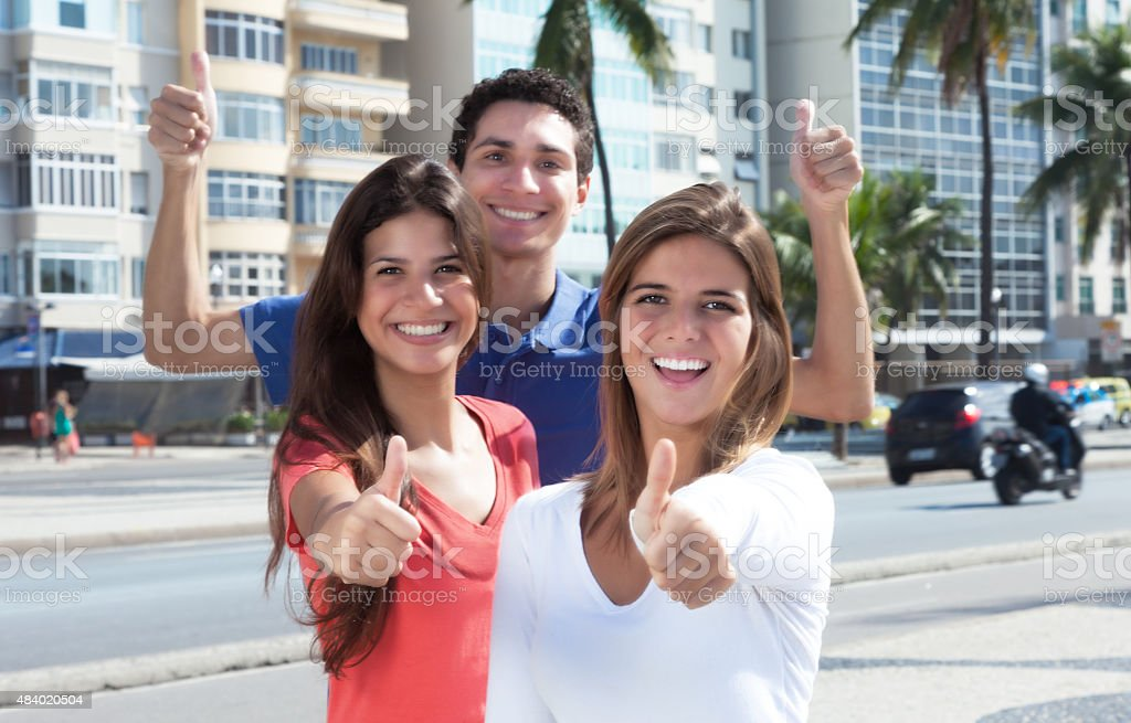 Tres jóvenes en la ciudad, mostrando pulgar arriba - foto de stock