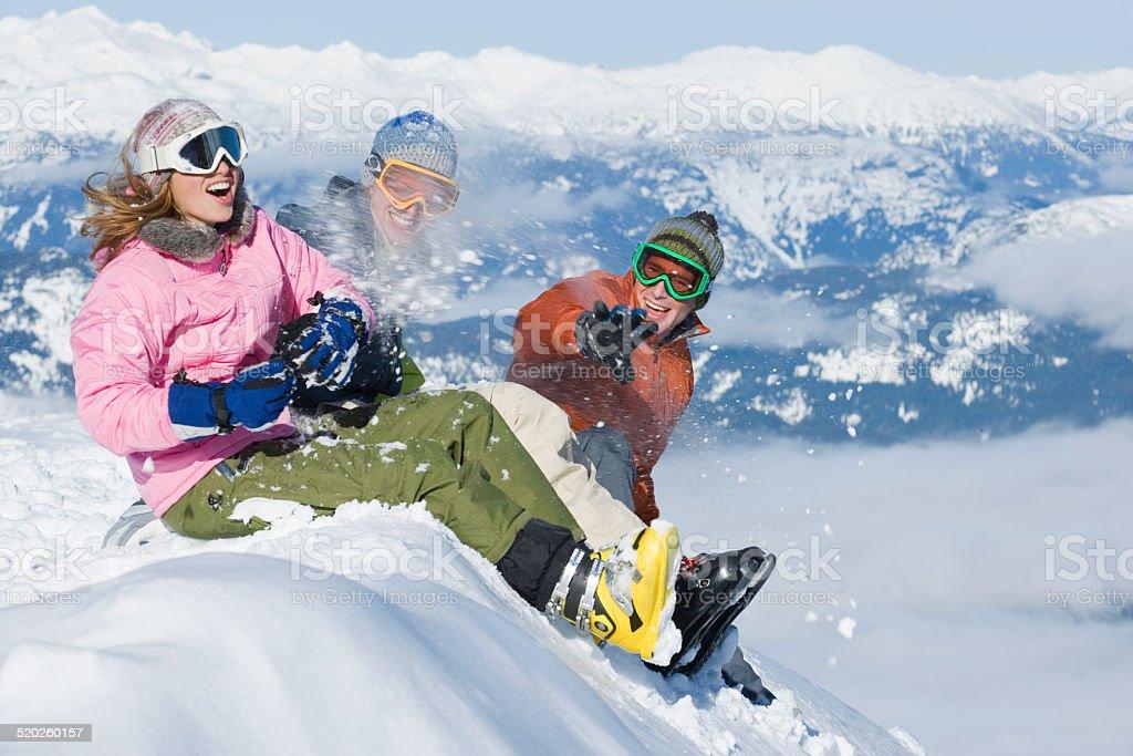 Trois jeunes assis sur la neige dans les montagnes paysage bank - Photo