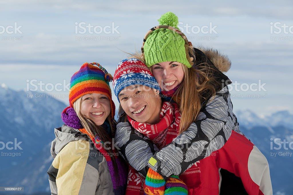 Three young people standing on mountain peak in winter royalty-free stock photo