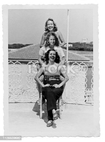Three young smiling women at the beach in 1938