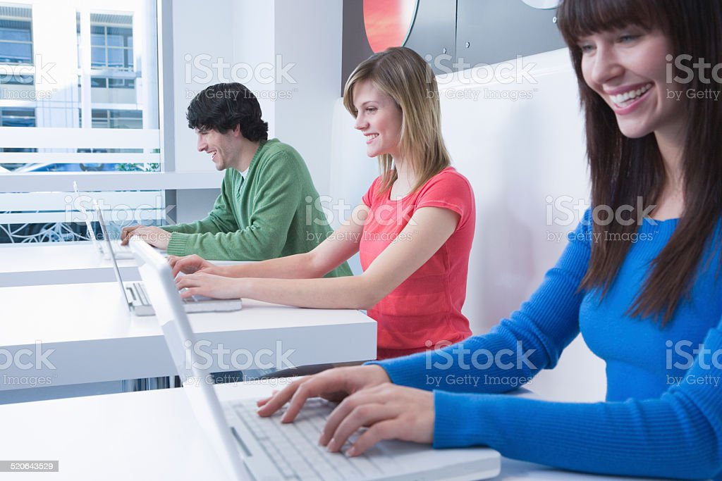 Three young woman sitting in row at cafe, smiling stock photo