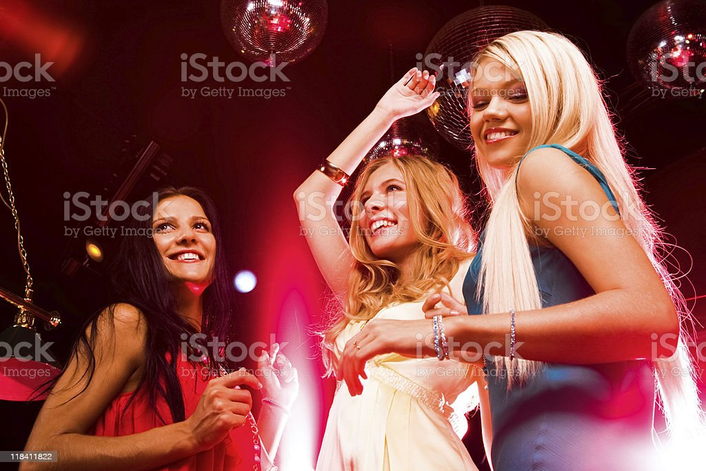 Three young woman smiling and dancing at a disco stock photo