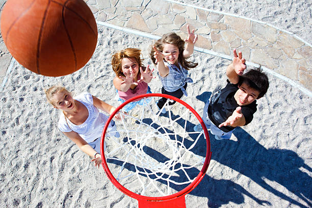 Three young women and a young man playing basketball stock photo