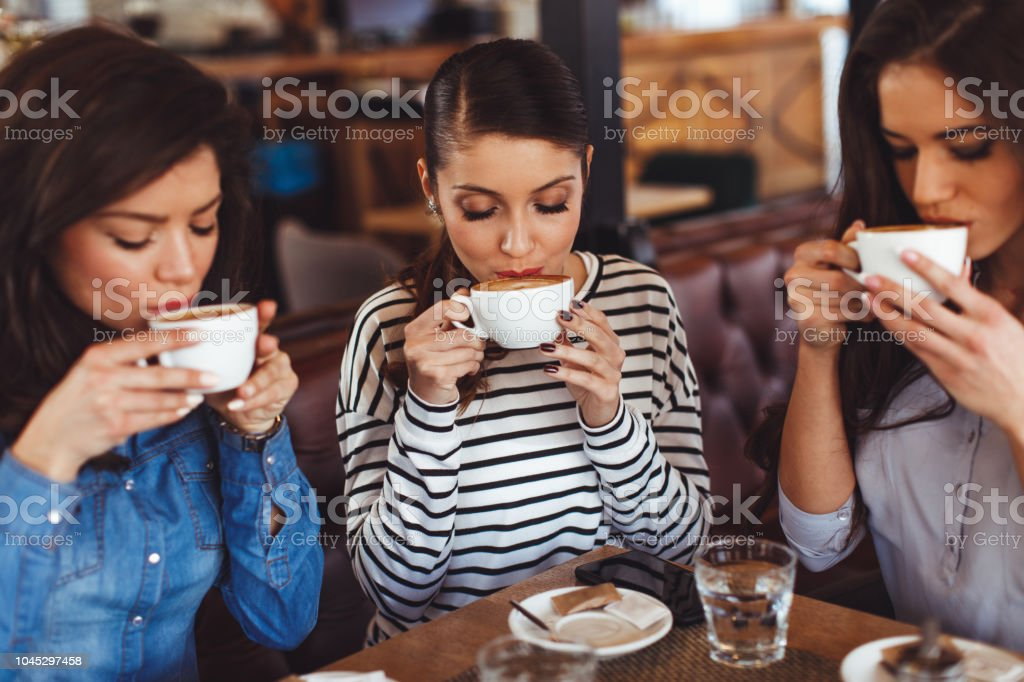 Three young women enjoy coffee at a coffee shop stock photo