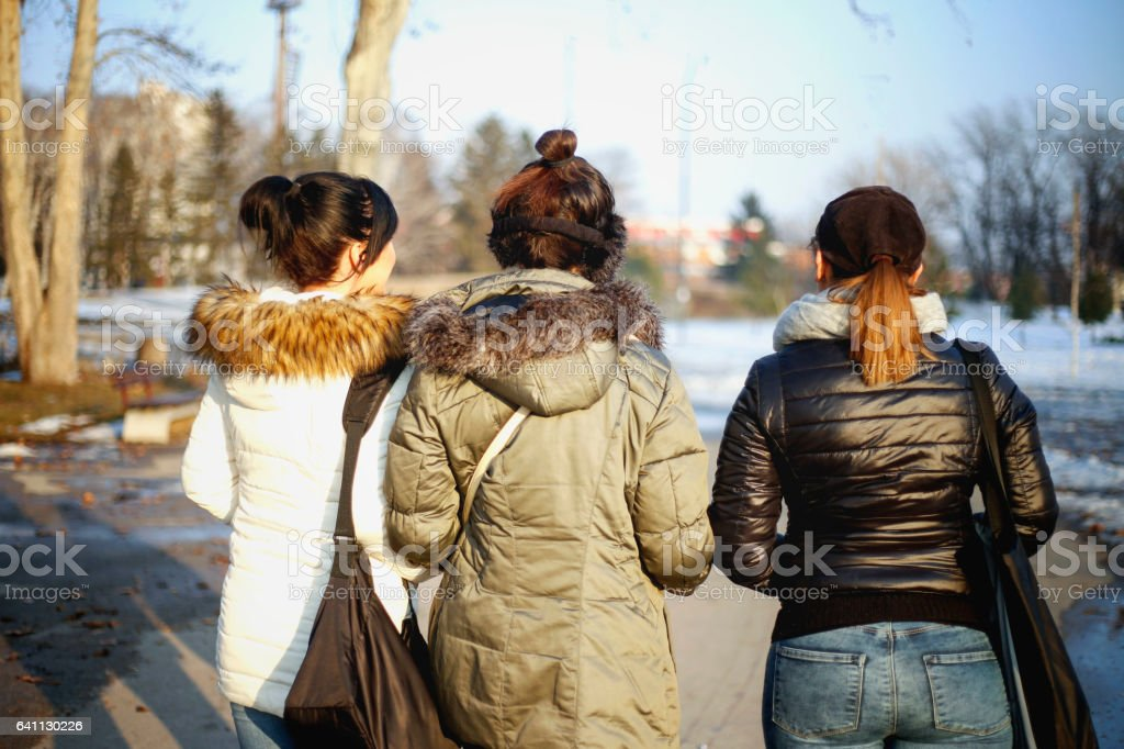 Three young women enjoying in sunny day in winter season stock photo