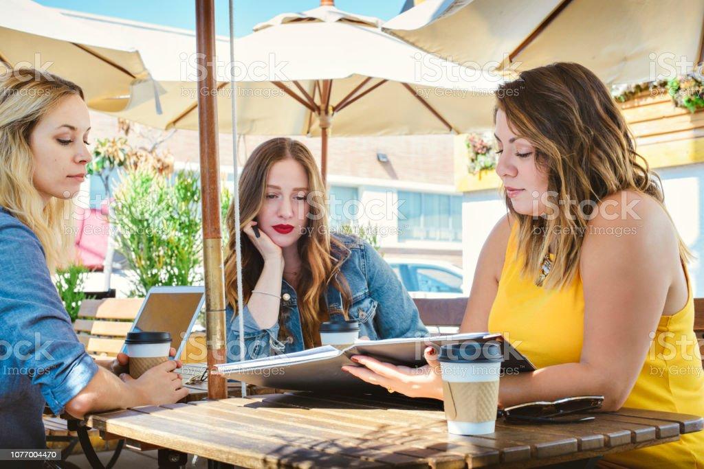 Drei junge Frauen haben einen Geschäftstermin in einem Coffee Shop – Foto