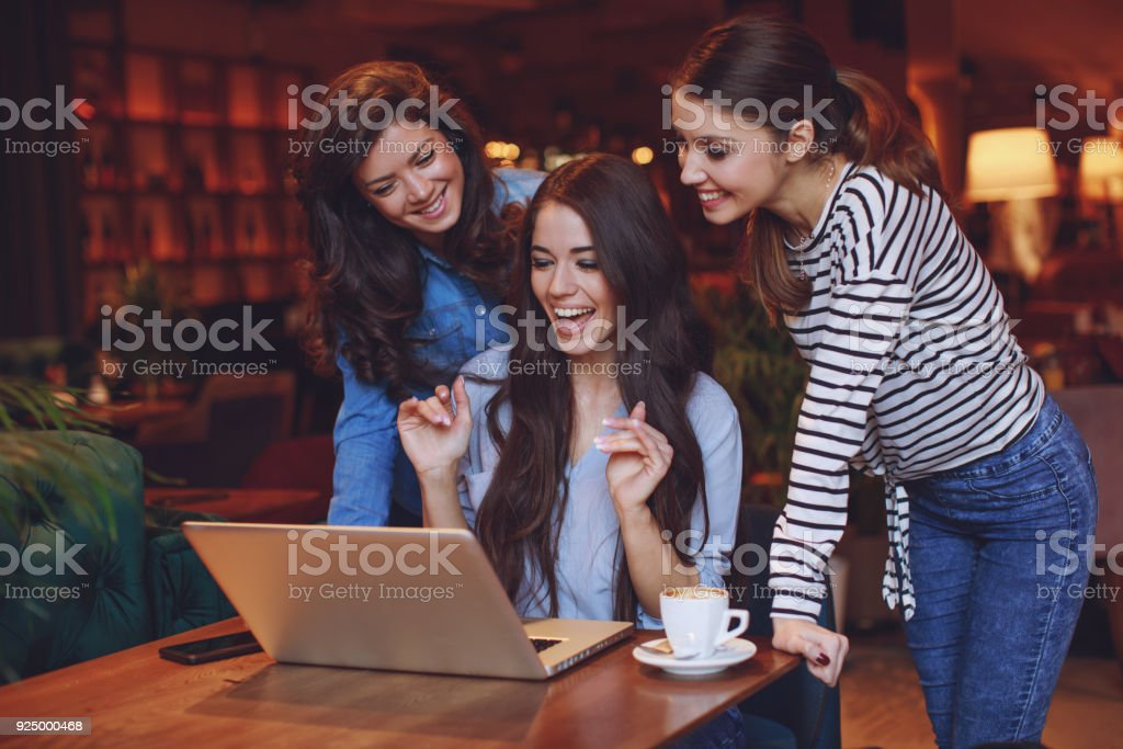 Three young women having fun with laptop in cafe stock photo