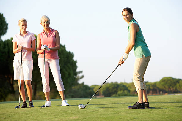 three young women holding clubs on a golf course - female golfer stock photos and pictures