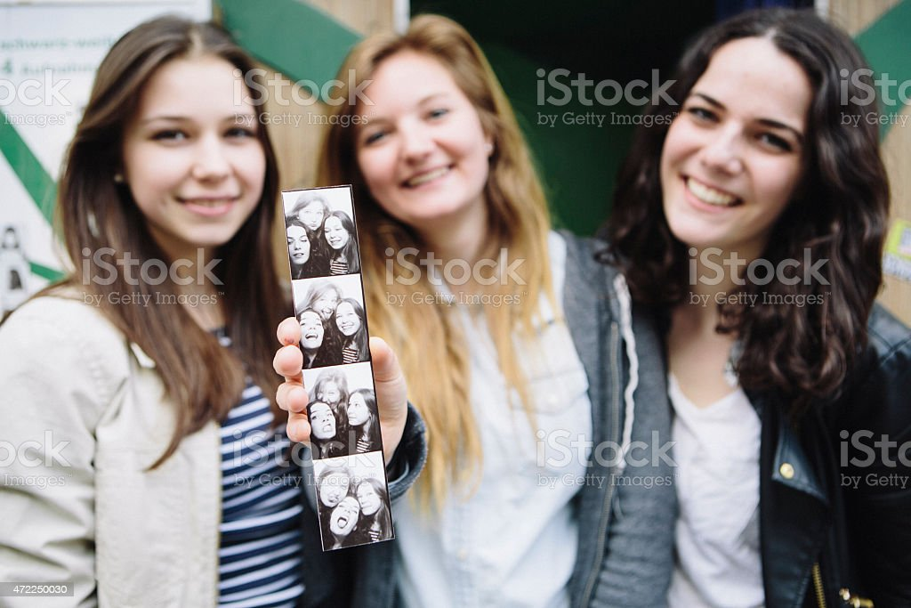 Three young women holding up pictures from a photo booth stock photo