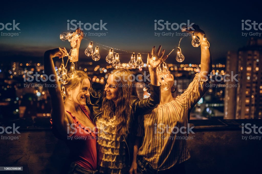 Three young women hugging on rooftop stock photo