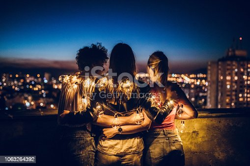 istock Three young women hugging on rooftop 1063264392