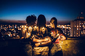Three female friends with string light, hugging on rooftop