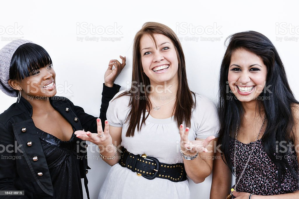 Three young women laughing, shrugging and gesturing royalty-free stock photo