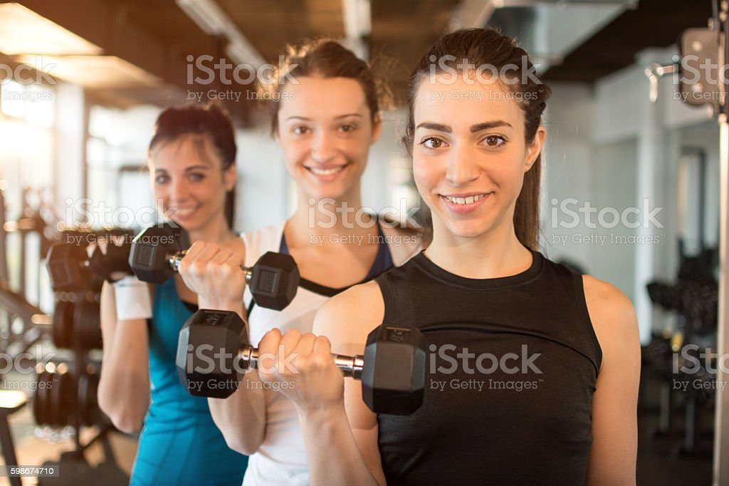 Three young women lifting weights in a fitness club. - foto de stock