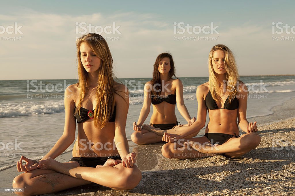 Three young women meditating on the beach royalty-free stock photo
